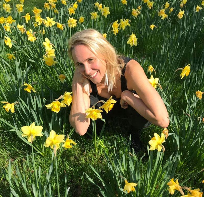 Samantha sitting amongst daffodils.