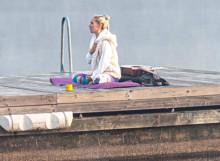 Samantha meditating on a jetty