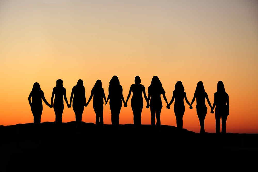 Silhouette of line of women in the sunset